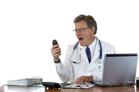 Aged male doctor in office has stress and screams into thelephone.. Isolated on white background.