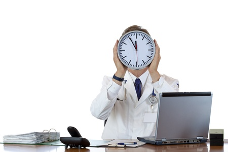 burnout: Stressed medical holds clock in front of face because of time pressure.Isolated on white background.