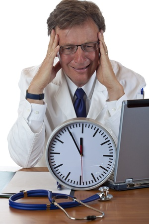 deceleration: Stressed medical with clock in front holds his head because of time pressure. Isolated on white background. Stock Photo