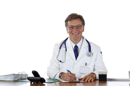 historia clinica: Sonriendo anciano m�dico escribe de registro del paciente. Freigestellt auf weissem Hintergrund. Foto de archivo