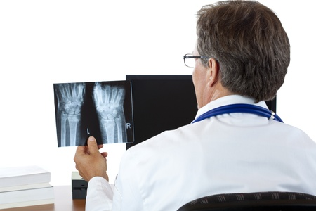 Rear view of an aged radiologist examining radiograph.Isolated on white background. Фото со стока