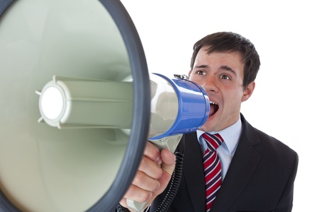 Closeup of a businessman roaring loudly into megaphone.Isolated on white background.