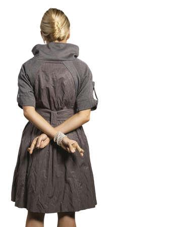 mani incrociate: donna che tiene le dita incrociate dietro la schiena Archivio Fotografico