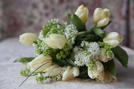 lilacs: Bouquet of white tulips and white lilacs on a table in interior Stock Photo
