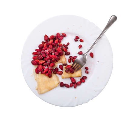 eaten: Delicious pancakes with strawberries and sugar on a white plate isolated. Half is eaten