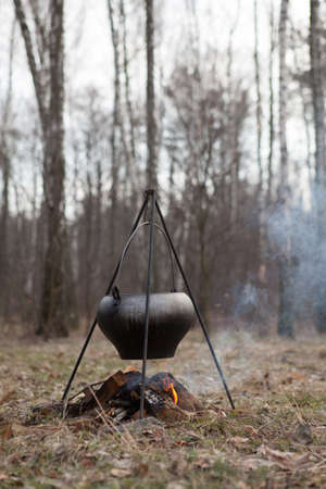 Cooking bogracs gulyas soup in a cauldron on fire in forest