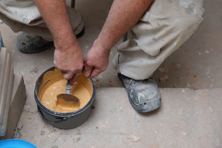 A worker mixes hand-dry cement grout in meringue color with water using a trowel. To fill the gaps between the ceramic tiles. Stok Fotoğraf