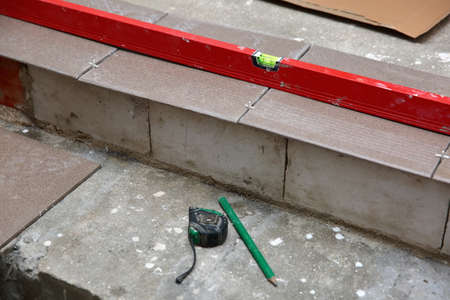 Planning the laying of terracotta on the stairs, while keeping an equal footing with the spirit level. Reklamní fotografie