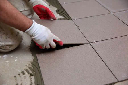 El constructor arregla baldosas de cerámica.