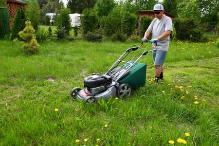 The man cuts the lawn with the mower in the backyard garden.