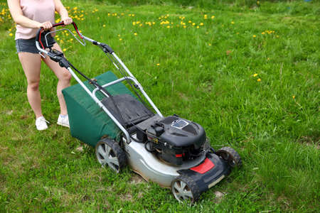 The teenager cuts the lawn with a petrol mower.