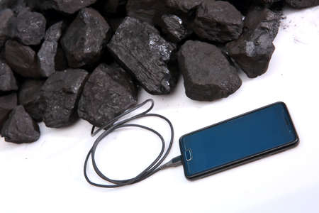 A smartphone connected directly to the hard coal prism is recharge the batteries. Ecological use of resources. Banco de Imagens
