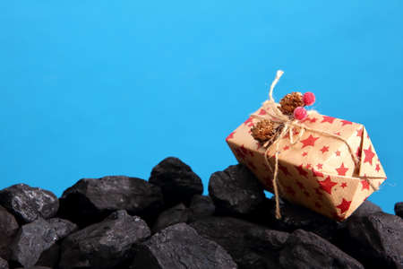 The package with the wrapped gift lies on a heap of black coal.