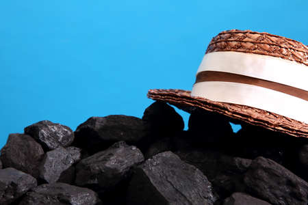 Black coal covered with straw hat symbolizing the ancient times.