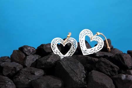 Decorative heart lying on pile of black coal.