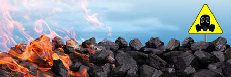 A pile of black coal burns and releases.