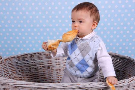 A tiny child eats a wicker basket in a basket woven from a wicker tree. Banco de Imagens
