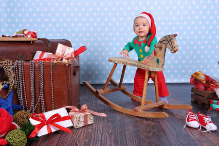 A small boy dressed up as an elf stands in Christmas decorations. Banco de Imagens