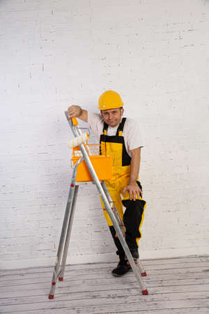 A professional painter compact and ready to work at any time. He is wearing typical protective clothing used at the construction site.