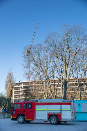 Fire truck and High tower crane on the finger of the construction of a new hotel being built in the center of Lublin in Poland.