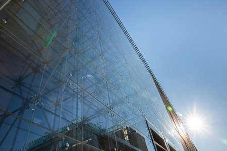 A modern and at the same time a tall building with a glass facade and steel fixings in full sun. Фото со стока