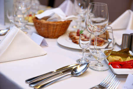 A huge table, covered with a white tablecloth with all the cutlery and food.