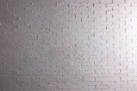 Brick painted white and properly illuminated reflects the interesting climate of its structure.