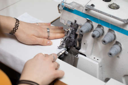 A young girl learns to sew on a specialized sewing machine.
