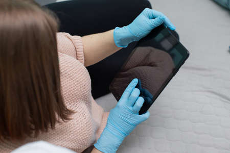 if the tablet is used by more people, for safety you have to put on rubber protective gloves so as not to get infected. Фото со стока
