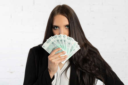 A young successful woman is holding a large amount of cash. 스톡 콘텐츠