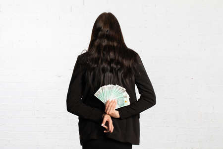 Behind her, the woman holds money as a surprise for the winner. 스톡 콘텐츠