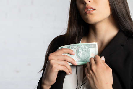 After a successful transaction, the woman puts a thick bundle of paper banknotes into her pocket.