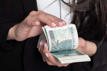 A close up shot when a businesswomen counts a thick stack of banknotes in Polish denomination. Reklamní fotografie