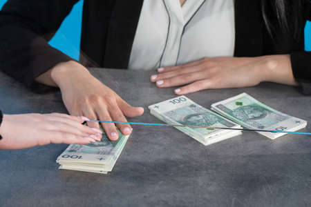 At a bank position, an employee accepts large sums of money from a young woman. 스톡 콘텐츠