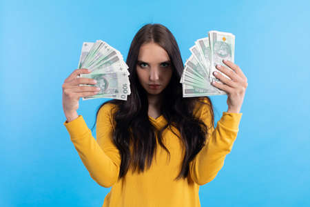 The teenager holds a large sum of money in her hand and is ready to give it to her.