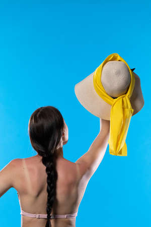 A young adult with braided hair holds a large hat high up. Banco de Imagens