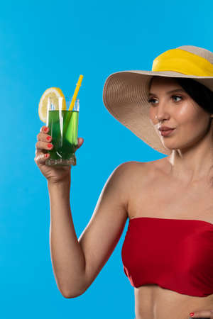 The young girl looks into the lens and holds a cold alcoholic drink in her hand. Stock Photo
