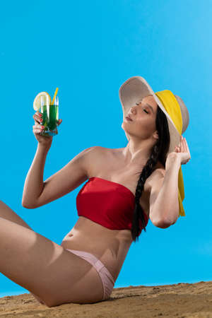 During hot summer, the teenager with a hat on her head holds an alcoholic drink in her hand. Imagens
