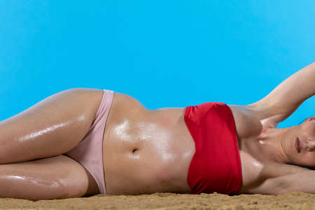 The girl in the holiday sun is sunbathing on the beach and her body is lubricated with moisturizing oil.