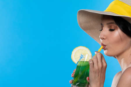 A teenager sipping a cold alcoholic drink through a straw during a hot summer.