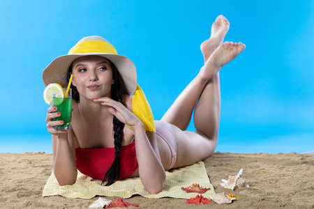 While sunbathing on the beach, a teenager drinks a cold alcoholic drink.