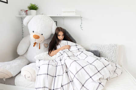 A young girl lies sick at home in her bed during illness.