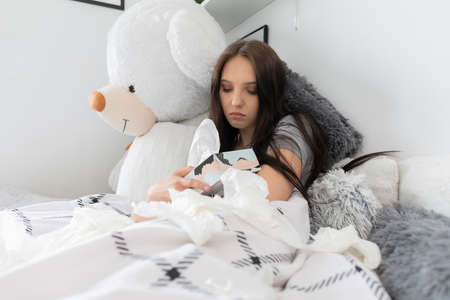 The teenager lying in bed takes out white handkerchiefs from a colored box. Stockfoto