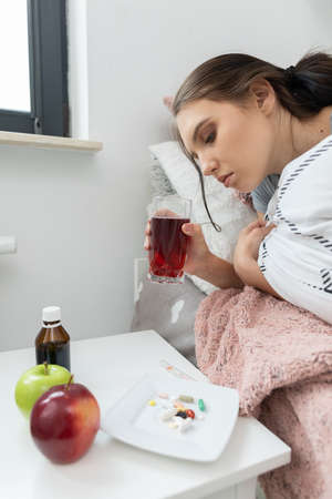 Hot tea with herbs. A young teenage girl lies sick from her bed. Acute cold. 免版税图像