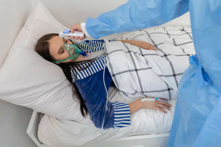 Patient temperature measurement. Young teenager. Oxygen mask on the face. Hospital bed in an infectious ward.