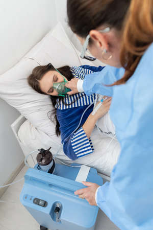 The teenager has a breathing ventilator connected. The doctor adjusts the respirator to give the right dose of oxygen.