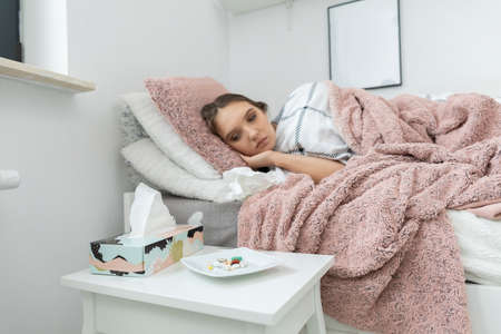 A sick teenager is lying on the bed. In front of the bed is a white table with a plate full of various tablets. 免版税图像
