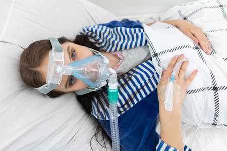 Oxygen mask attached to the respiratory tract. The teenager lies in a hospital bed. A seriously ill young girl. 免版税图像