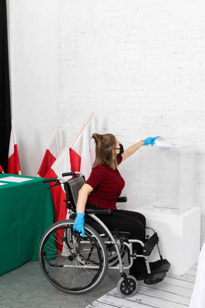 Difficulties in throwing into the ballot box. Teenager in a wheelchair. Voting for the Polish president.