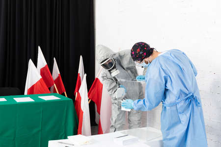 Two men clean and disinfect the polling place just before the start of the presidential election in Poland.